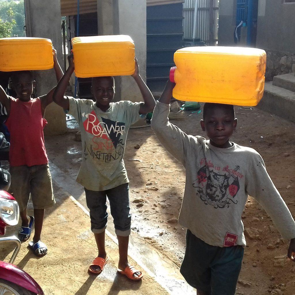 Jongens Dragen Jerrycans Met Water Op Hun Hoofd In Bunia.